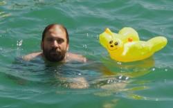 Matthias nageant dans la Limmat tenant en laisse un papillon en plastique gonflable