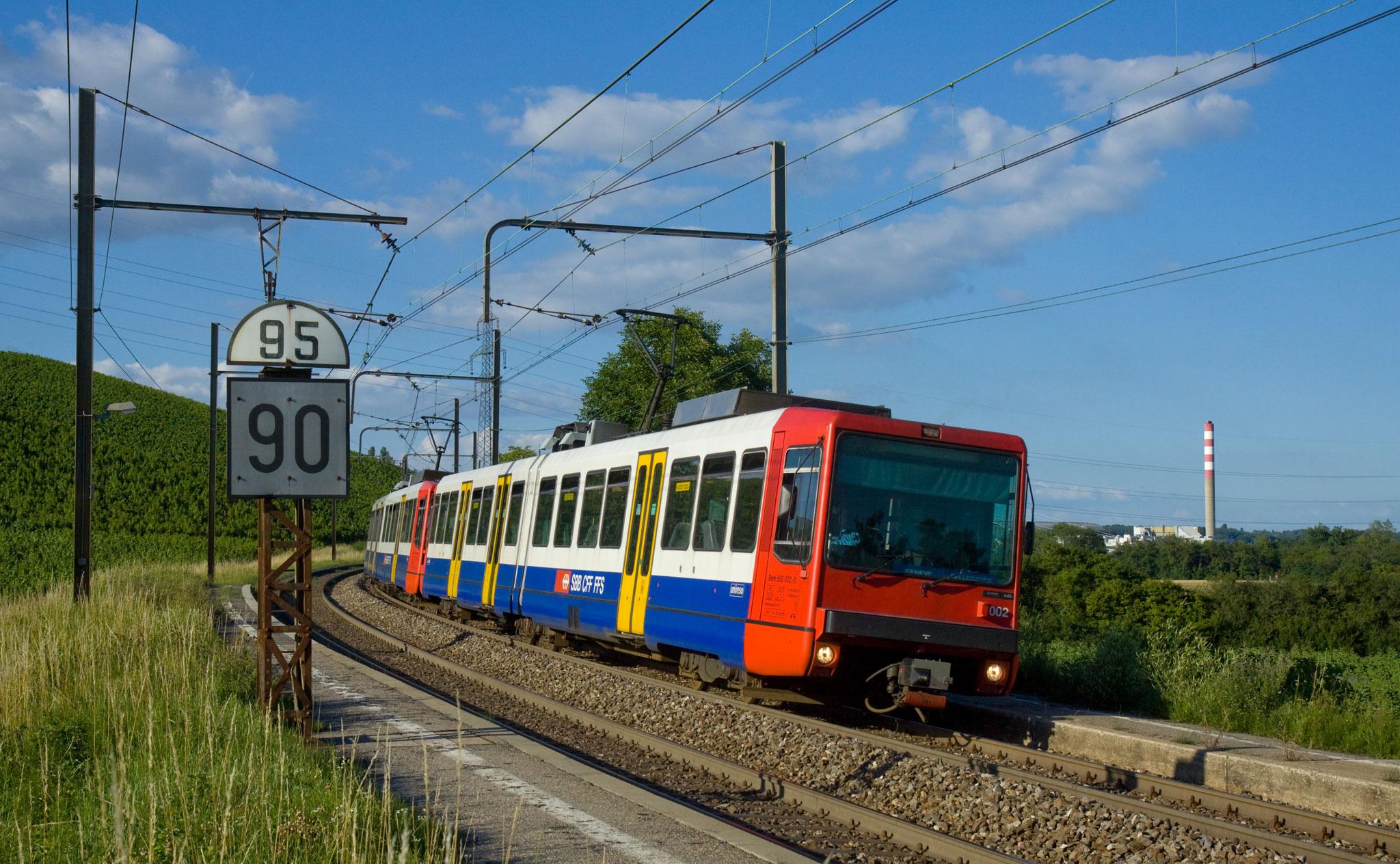 Une rame de train rouge, blanche et bleue dans une courbe dans la campagne