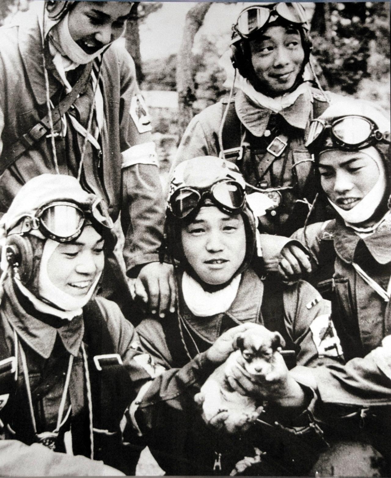 Caporal Yukio Araki (agé de 17 ans) tenant dans ses mains un chiot, entouré de quatre autres jeunes gens du 72e régiment Shinbu