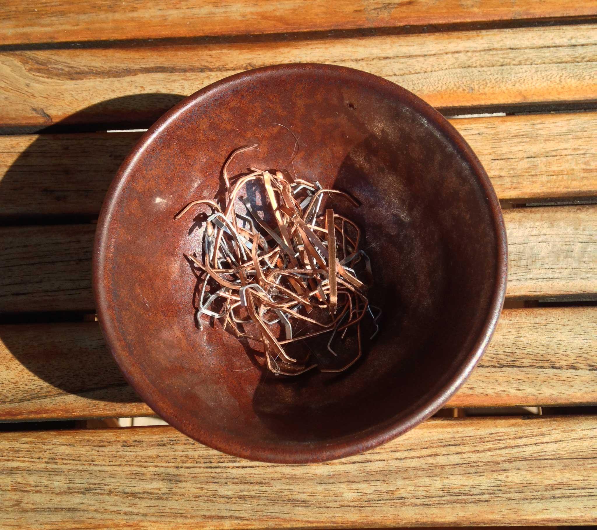 Bol à thé rouille avec des agrafes cuivrées sur une table en bois